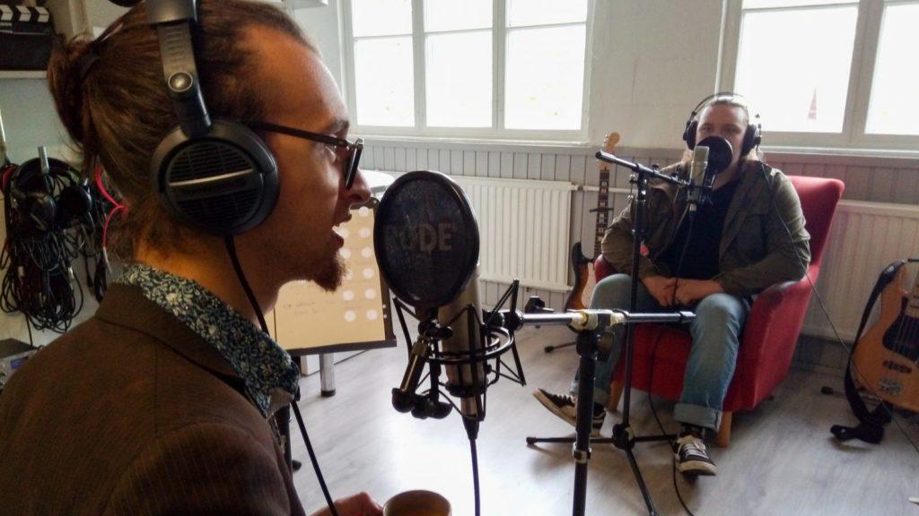 Kaksi opiskelijaa mikrofonien äärellä