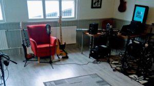 Ääniraudan studio, punainen nojatuoli, jonka edessä on mikrofoni ja äänityslaitteisto sen vieressä