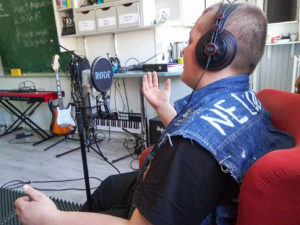 Opiskelija kuulokkeet päässä puhuu mikrofoniin, takaapäin kuvattuna