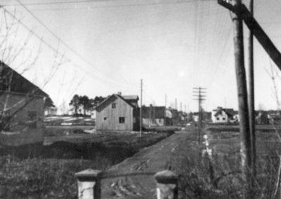 Mustavalkoisessa valokuvassa päällystämätön tie halkoo peltoja ja tienlaidassa on muutama talo.