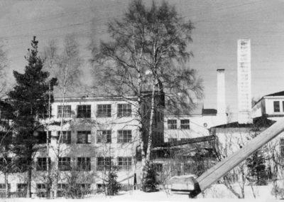 Mustavalkoinen kuva talvisista tehdasrakennuksista.